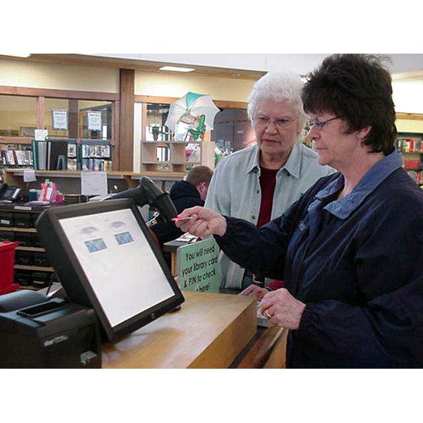 2008 - Lorena helping library user with the new self-check unit